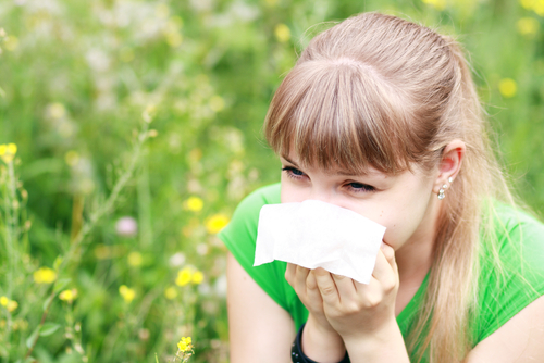 Allergies - woman sneezing outside