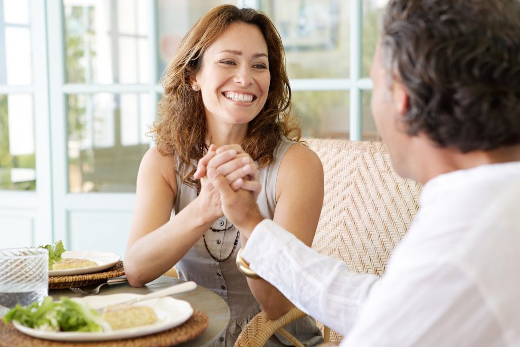 couple-holding-hands-at-table