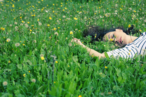 Woman laying in grass field